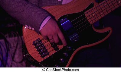 Bass Guitar close up. Man playing guitar at rock concert. 4k UHD video