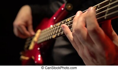 Bass guitar. Fingers fingering the strings. Close up. Black...
