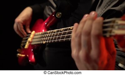 Bass guitar. Man fingers fingering the strings the musician . Close up. Black background