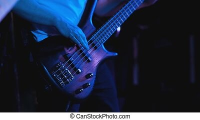 Black electric guitar bass, performing at concert