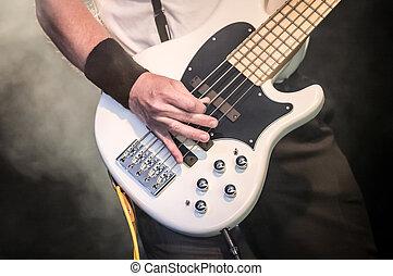 bass guitar - hand of a musician playing a five string bass...