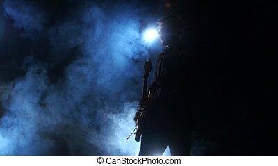 Bass guitar. Playing professional musician in a dark smoke studio