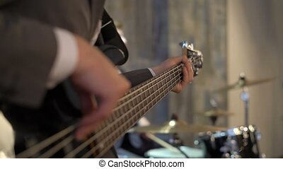 Bass guitarist in suit plays music with drummer. Black bass...