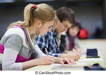 bastante, hembra, estudiante universitario, sentado, en, un, aula, lleno, de, estudiantes, durante, clase, (shallow, dof;, color, toned, image)