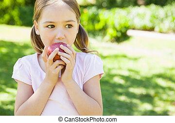 bastante, niña joven, manzana que come, en el estacionamiento