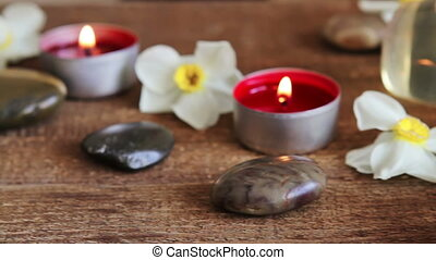 Spa still life containing bath salt, rocks, massage oil, candles and flowers
