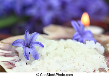 Bath salts in a seashell with candles glowing in the background.