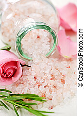 Pink bath salts in a glass jar with flowers and herbs