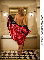 Bath time - Woman in red bath robe gets ready for luxury...