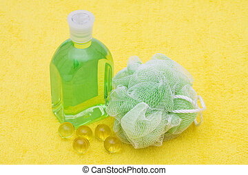 Bath Time - A sponge with bath beads and soap on a yellow...