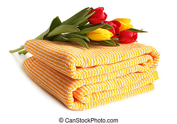 Bath towel with fresh tulips on white background