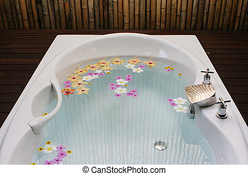 Bath tub filled with flowers in a modern spa.