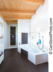 bath with bathtub in timber house and dark brown tiles floor