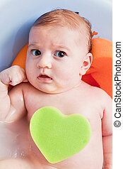 Bathing a young 3 months baby with a heart shaped sponge -...