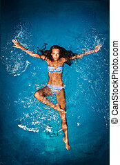 Bathing in blue. - A sexy tanned lady in a colorful bikini...