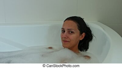 Bathing with bubble - Naked woman is relaxing in bathtub in...