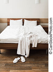 Bathrobe over bed in hotel room with slippers