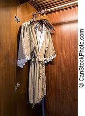 bathrobe with wooden hangers in wardrobe