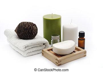 Bathroom composition with soap, essiantil oil, towel, soap dish, candels.