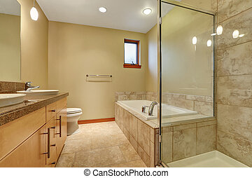 Bathroom interior in beige tones with vanity cabinet with granite counter top, tile floor, shower and bath tub. Northwest, USA