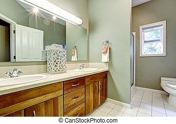 Bathroom interior in soft mint color with white tile floor and wooden cabinet with mirror