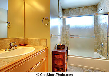 Bathroom interior with stone tile, wood cabinet and tub.