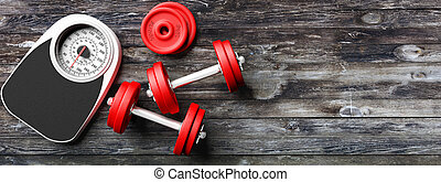 Bathroom scale, dumbbells on an old wooden floor background....
