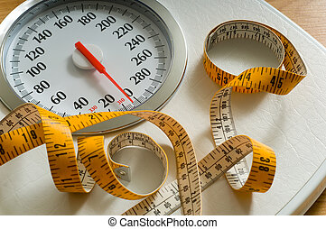 Bathroom scale with large dial and tape measure. Theme of dieting or living healthy