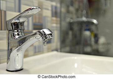 Bathroom tap leaking water drops