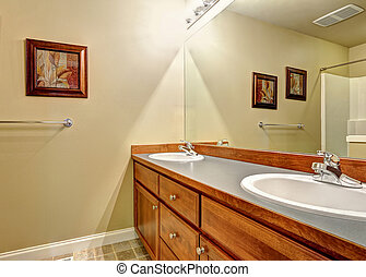 Brown bathroom vanity cabinet with two sinks and mirror.