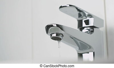 Bathroom. Water dripping from chrome-plated faucet