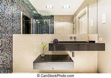 Bathroom with minimalistic sink and mosaic wall