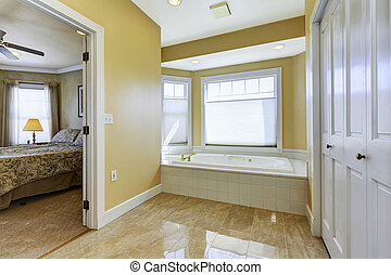 Soft tones bathroom with windows and shiny tile floor