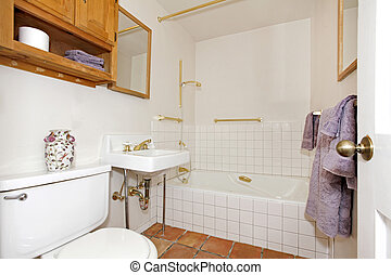 Bathroom with white tiles tub with gold details