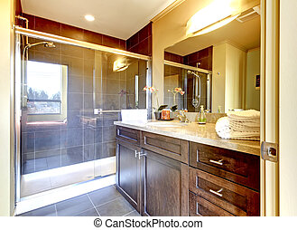 Bathroom with wood cabinet and glass shower.