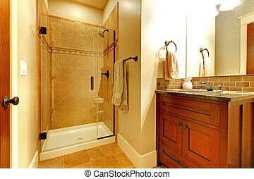 Bathroom with wood cabinet and tile shower. - Bathroom with...