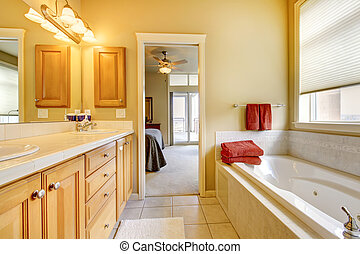 Bathroom with wood cabinets and tub.