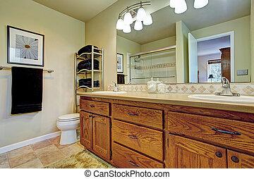 Bathroom wtih wooden vanity cabinet and mirror