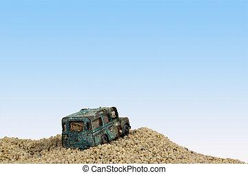 Battered Blue Toy Car in Sand Pit Against Blue Sky