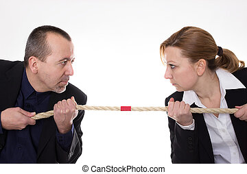 Battle of the sexes - Man and woman pulling a rope against...