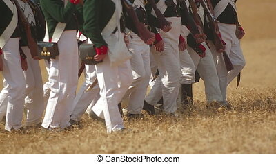 Battle reenactment - Troops marching along a field during a...