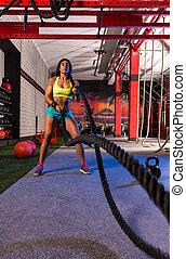 battling ropes girl at gym workout exercise