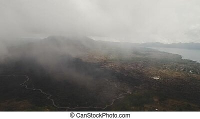 Mountain landscape with volcano, traces of lava on the ground, sky with clouds. Aerial view of Mount Batur Volcano in Kintamani. Bali volcano, also referred to as Kintamani is popular sightseeing destination in Bali. Travel concept. Aerial footage.