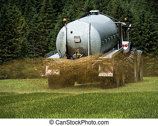 bauer fertilizes a field with manure - a farmer goes with...
