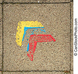 Paving stone with three painted arrow heads, yellow, blue and red symbolising bauhaus.