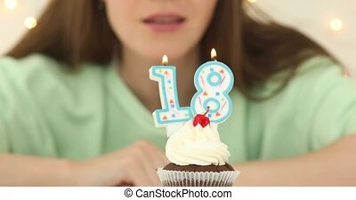 bautiful caucasian girl blowing 18 candles on cake