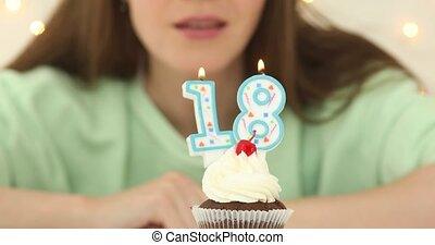bautiful caucasian girl blowing 18 candles on cake