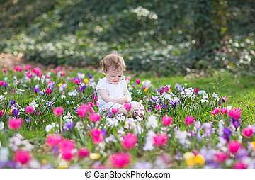 Bautiful funny baby girl playing in a field of flowers
