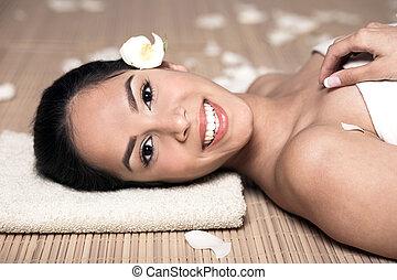 bautiful, mujer sonriente, acostado, para, tratamiento del balneario