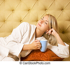 Bautiful young woman sitting on a bed and drinking cofee in ...